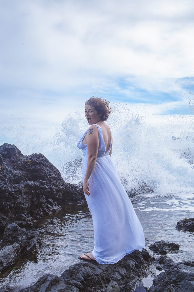 Woman standing in front of large wave Adventure Session Portrait Photography big island hawaii