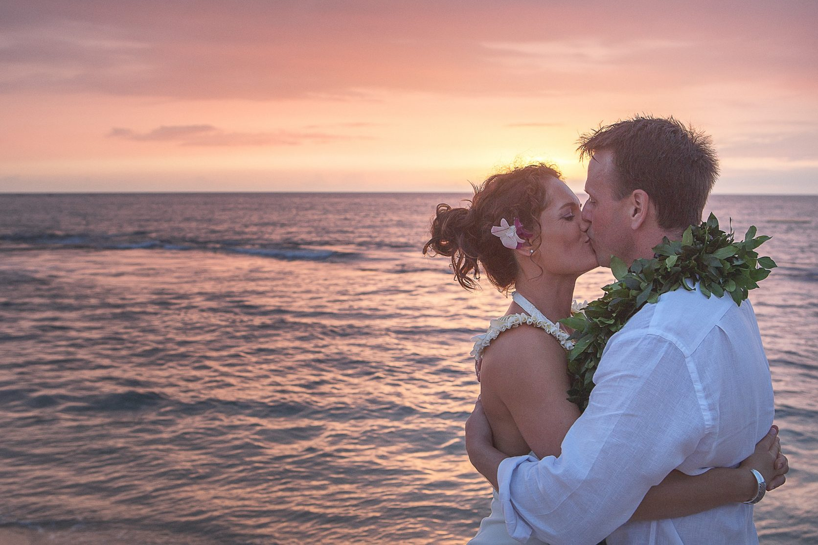 Newlyweds kissing at sunset kukio beach Big Island Hawaii