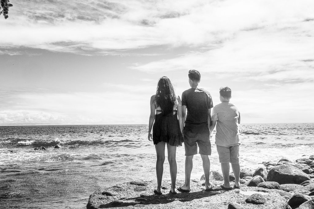 Black and white brothers and sister facing ocean Family portrait photography kolekole beach park big island hawaii