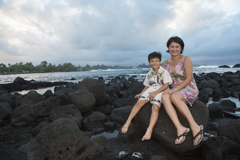 mother and son sitting on rocks near ocean Portrait Photography Richardson ocean park hilo big island hawaii