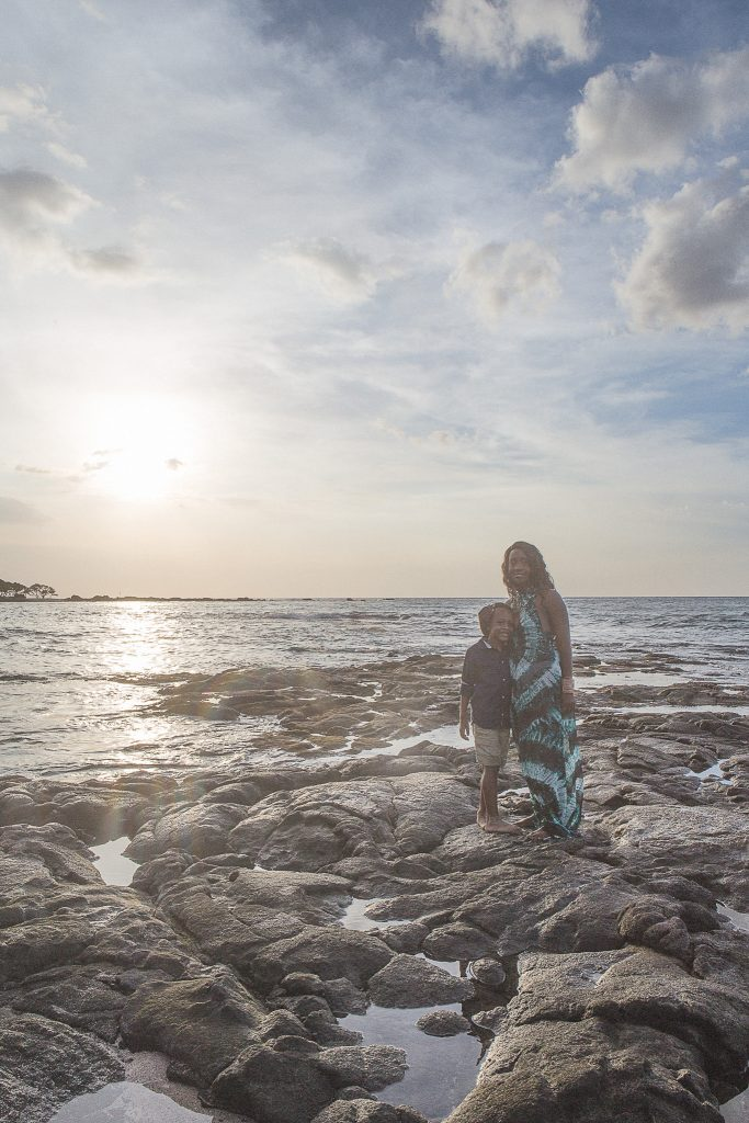 mother and son standing on rocks near ocean Kukio Beach Portrait Photography Kailua-kona big island hawaii
