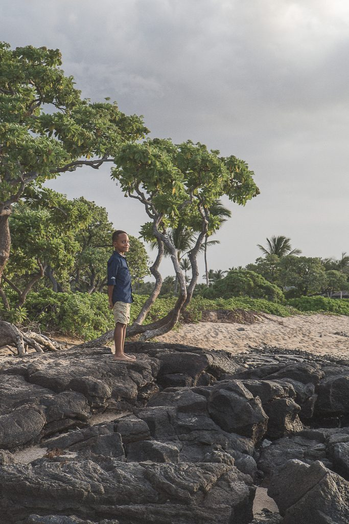 young boy standing on rocks Kukio Beach Portrait Photography Kailua-kona big island hawaii