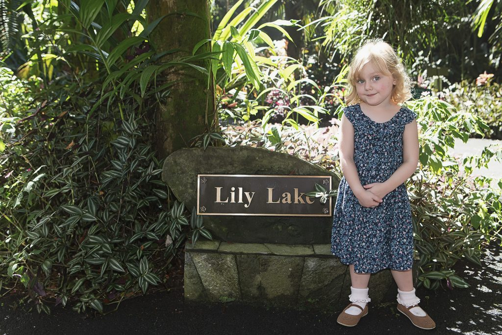little girl standing by sign for lily lake hawaii portrait Photography Hawaii tropical botanical garden big island Hawaii