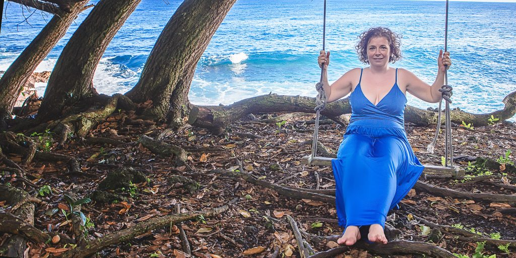 woman in blue dress on swing near cliff and ocean Adventure Session Portrait Photography big island hawaii