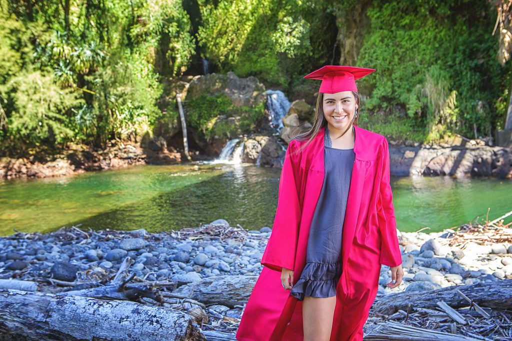 Senio girl cap and gown in front of waterwall Family portrait photography kolekole beach park big island hawaii