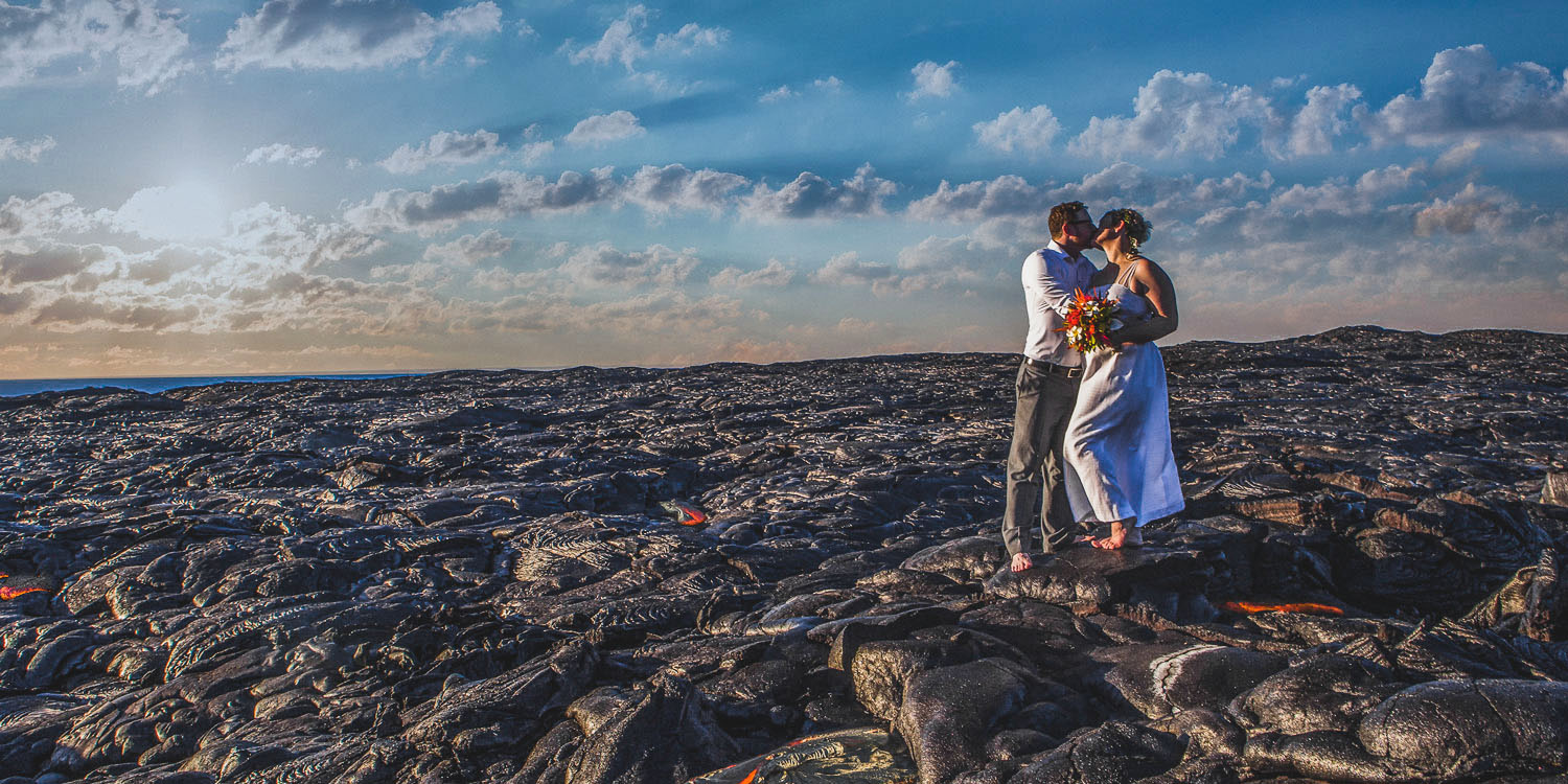 Bride and groom kissing near flowing lava Big Island Hawaii