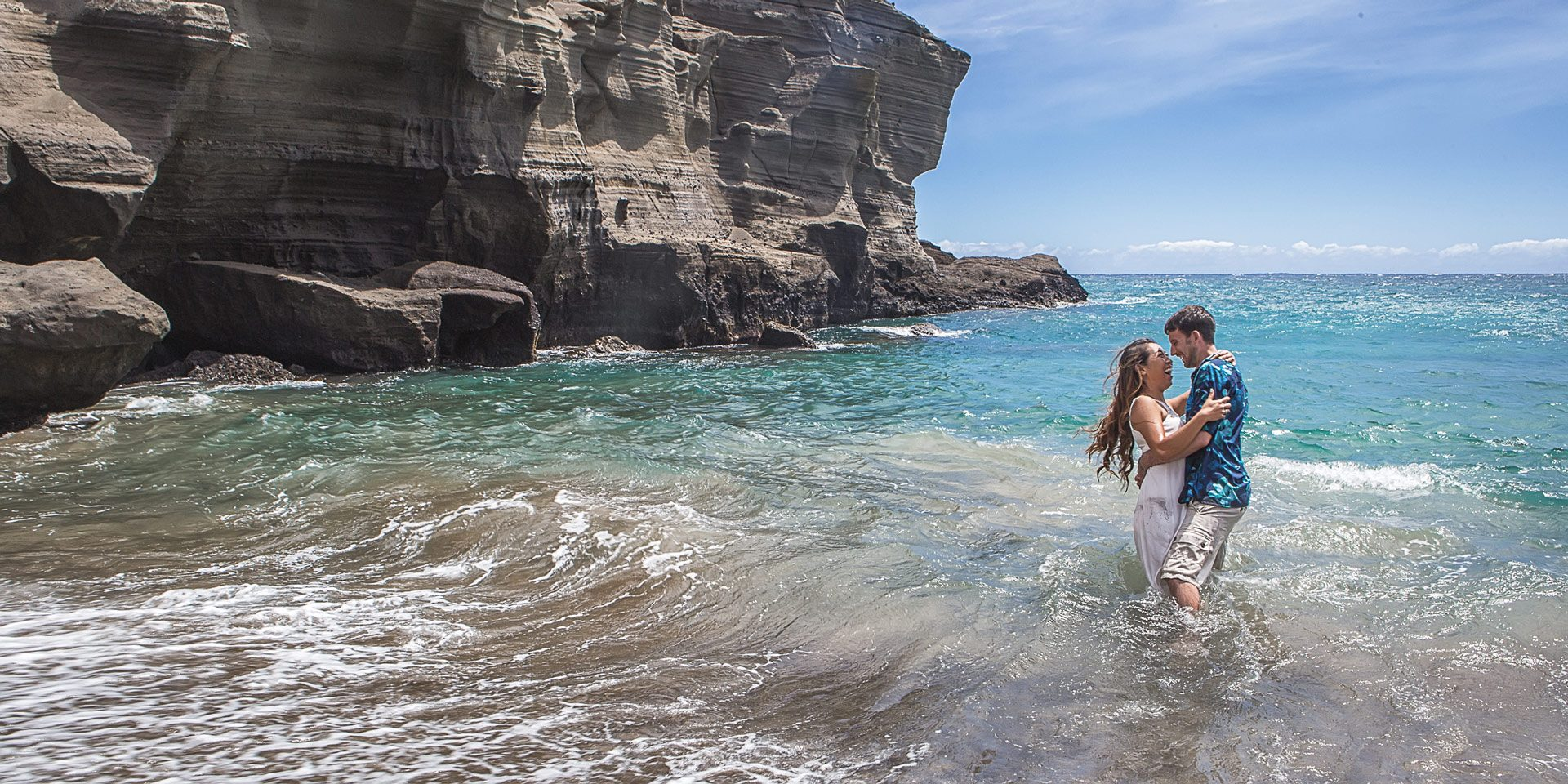 Couple laughing in waves green sand beach big Island Hawaii