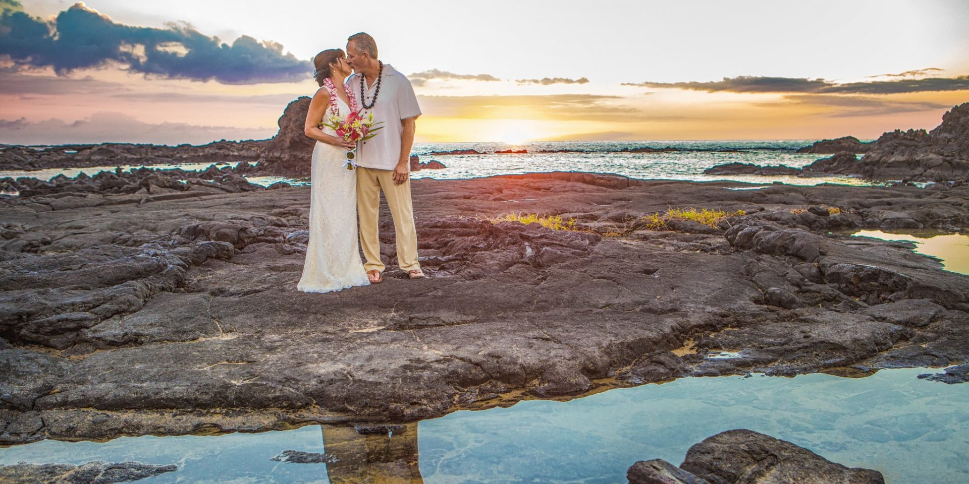 Newlyweds kissing on lava rock at sunset Kikuau Point Big Island Hawaii